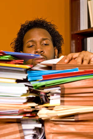 inundated: A young African American male buried in work strains to look inside a folder on the top of a stack of colorful folders piled on his desk. Stock Photo