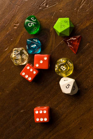 side lighting: Multicolored role play dice sitting on a wooden table top. Side lighting and depth of field used to add drama to the photo.