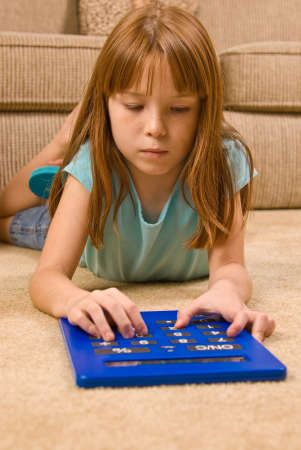 oversized: A young red headed female child lays on the floor and works on an oversized calculator.