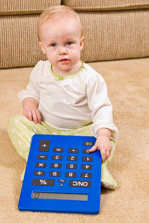 oversized: A young baby in a pair of generic PJs sitting on a living room floor with a large oversized calculator.