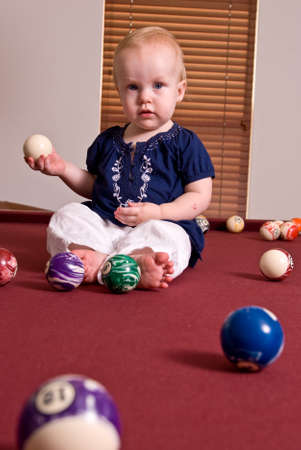pool balls: A young child sitting on a billiard table playing with the pool balls. She holds a cue ball in here hand and looks at the camera. Stock Photo