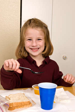 Young school girl eating lunch Stock Photo