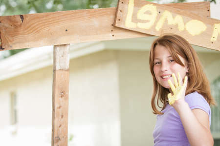 A girl with paint on her hand about to put a hand print on a lemonade stand sign