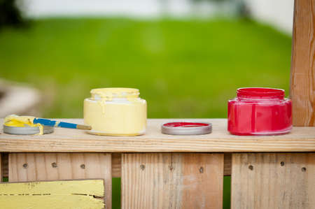 dominant color: Two open paint containers and a paint brush sitting on a wood booth