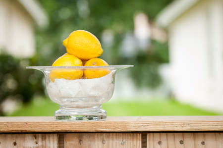 dominant color: Lemons in a glass bowl at an outdoor lemonade stand