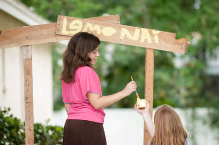 communications tools: Two young girls painting a lemonade stand sign