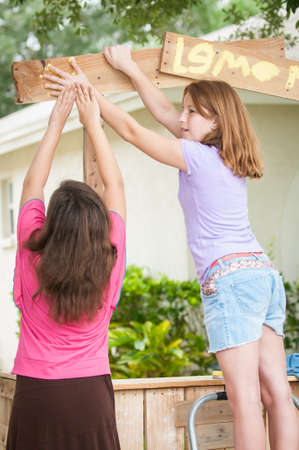 dominant color: Two young girls work together to paint a hand print on a  lemonade stand sign