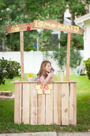 Bored young girl waiting on customers at her lemonade stand