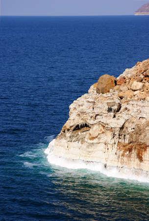 caked: Dead sea with salt caked on rocks