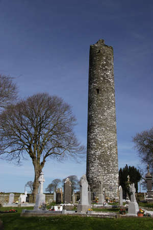 monastic: Monastic round tower in grave yard, ireland and blue sky Stock Photo