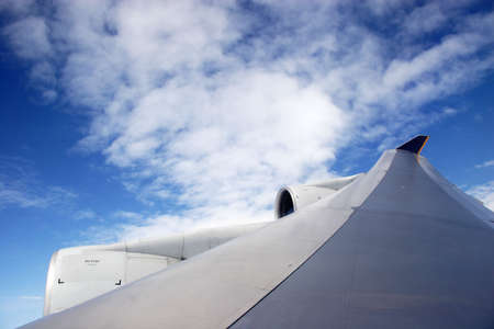 Plane wing with white clouds midflight Stock Photo