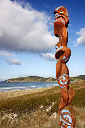 Maori carving overlooking Omaha beach, New Zealand Stock Photo