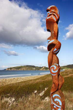 overlooking: Maori carving overlooking Omaha beach, New Zealand Stock Photo