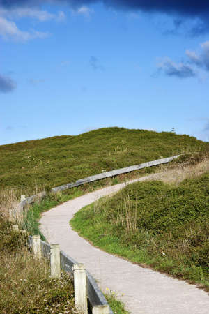 Walkway on dunes by beach Stock Photo