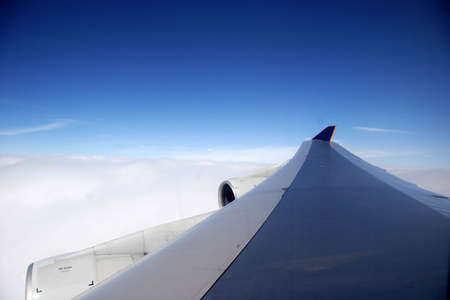 plane wing on a blue day mid flight