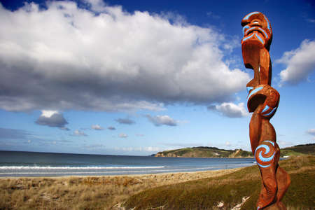 Maori carving guarding Omaha beach, New Zealand photo