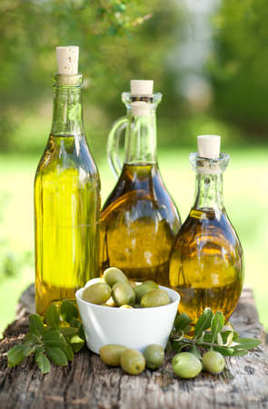 olive  oil: Fresh olive oil on wooden ground Stock Photo