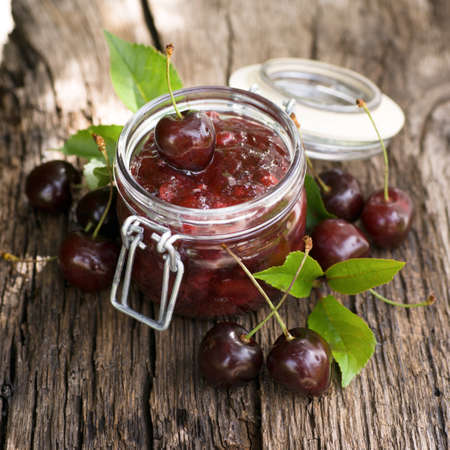 sour cherry: Fresh cherry jam in a preserving glass Stock Photo