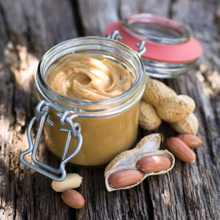 peanut butter and jelly: Fresh peanut butter on wooden ground