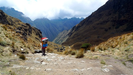 Porter and Inca Trail at Dead Woman Pass, on way to Machu Picchu, Peru Stock Photo