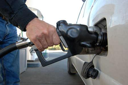 tanque de combustible: Cerca de la mano de un cliente de bombeo de combustible en el tanque de gasolina del coche.