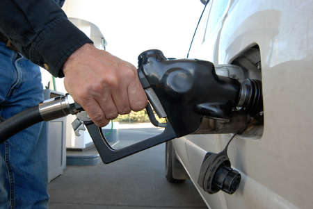 Close up of a customers hand pumping fuel into cars gas tank. Imagens