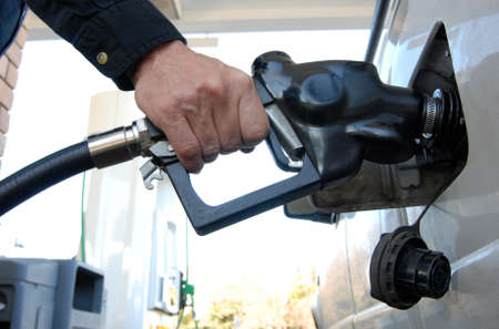 pricey: Close up of a customers hand pumping fuel into cars gas tank. Stock Photo