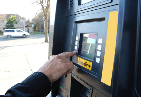 Close up of customers hand pushing buttons on a gasoline fuel pump photo