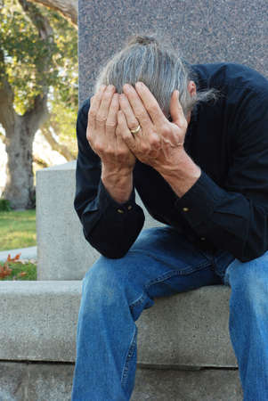 gravesite: Man sitting at gravesite with his head in his hands