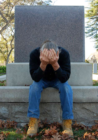 Man sitting at gravesite with his head in his hands