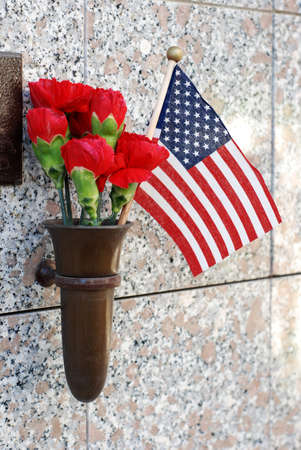 veteran's day: Red flowers and a small American flag at cemetery crypt  Stock Photo