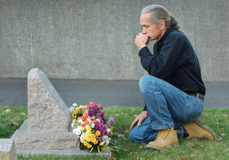 Man sitting at gravesite with a look of sadness