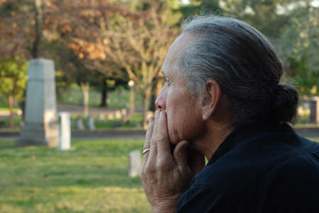 gravesite: Man sitting at gravesite with a look of sadness