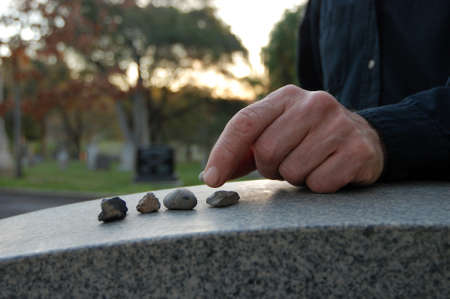 Close up of a left hand leaving a pebble on a headstone in cemetery