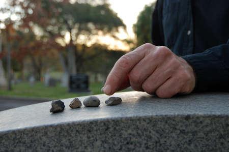 Nahaufnahme eines linken Hand verlässt einen Kieselstein auf einem Grabstein auf dem Friedhof Standard-Bild - 12566016