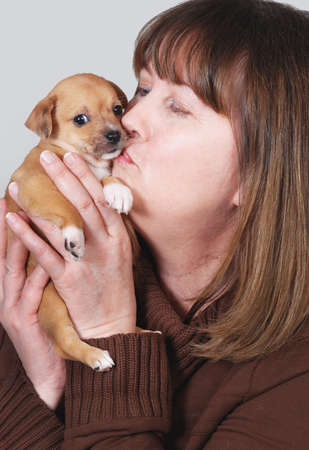 spay: Woman kissing chihuahua puppy