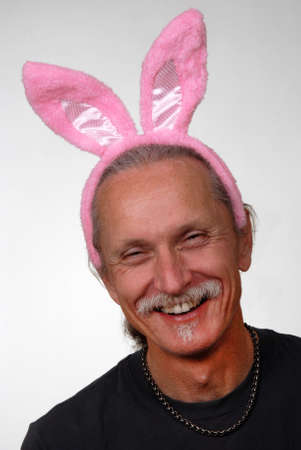 Laughing man wearing pink rabbit ears  photo