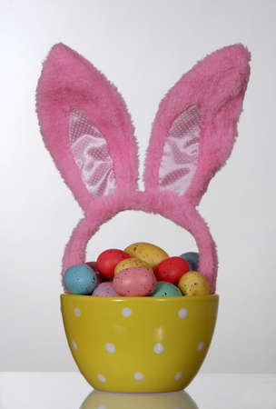 Easter eggs in a polka dot bowl, with pink rabbit ears Stock Photo - 12566034