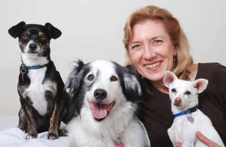 Smiling woman with three dogs