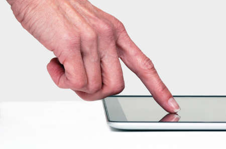 Close up of a finger touching e-tablet 版權商用圖片