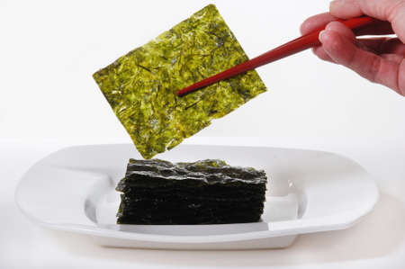 Roasted Seaweed, held with red chopsticks.  Isolated on white photo