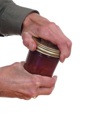 jam jar: Close up of hands opening a jar. Stock Photo