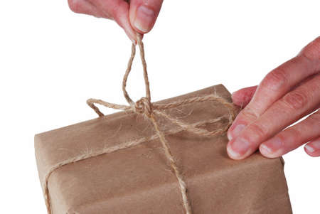 Close up of hands untying string on a package