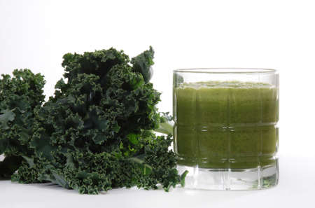 Fresh kale leaves near juiced kale beverage.