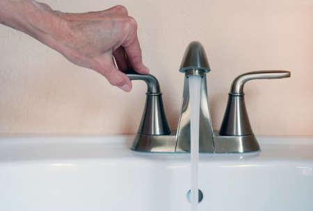 llave de agua: Primer plano de mano y la llave del grifo del fregadero, agua corriente.