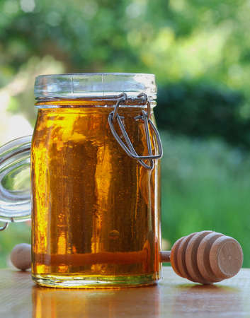A jar of honey with stir stick, natural outdoor background photo