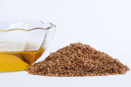 flaxseed: Flaxseed oil in bowl and whole flax seeds.  Isolated on white. Stock Photo