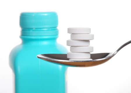 generic drugs: Compresse antiacido su un cucchiaio, una bottiglia di antiacido sfocato sullo sfondo Archivio Fotografico