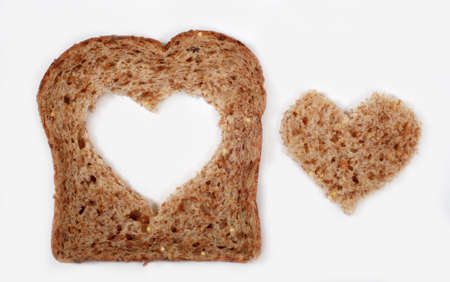 A slice of whole wheat bread with a heart shape cut from the center