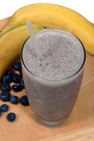 leche de soya: Batido de plátano, fruta de arándanos en un vaso cerca de la fruta fresca, orgánica Foto de archivo